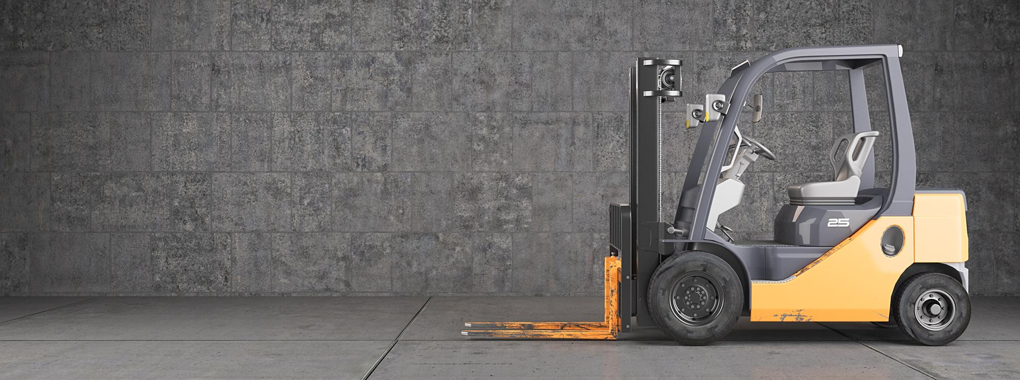 Forklift truck standing on industrial concrete wall background